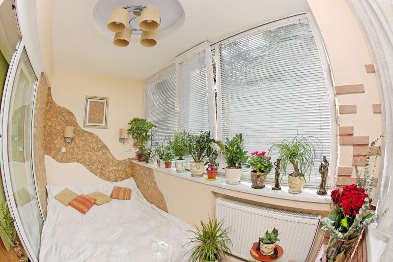 Sonniges Schlafzimmer auf Balkon mit Fenster und Anlagen stockfotografie