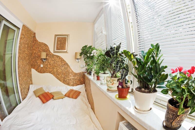 Sonniges Schlafzimmer auf Balkon mit Fenster und Anlagen, f stockbild