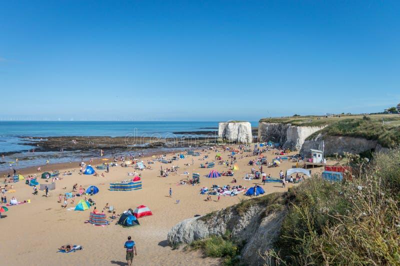 Sonniges Wetter holte Touristen und Besucher zur Botanik-Bucht setzen nahe Broadstairs Kent auf den Strand lizenzfreies stockbild