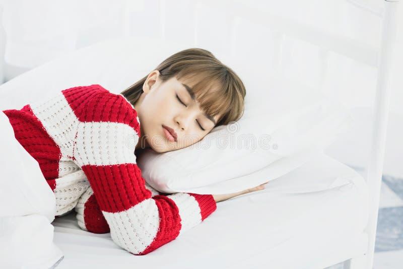 Sonno asiatico della donna sul cuscino bianco sul letto in camera da letto nella festa felice rilassi il tempo immagini stock libere da diritti