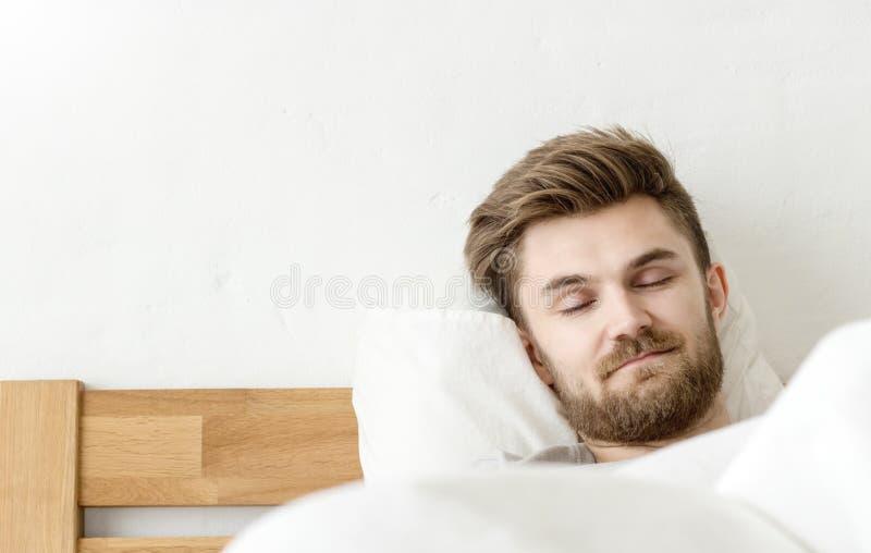 Sonno degli uomini sul letto immagine stock