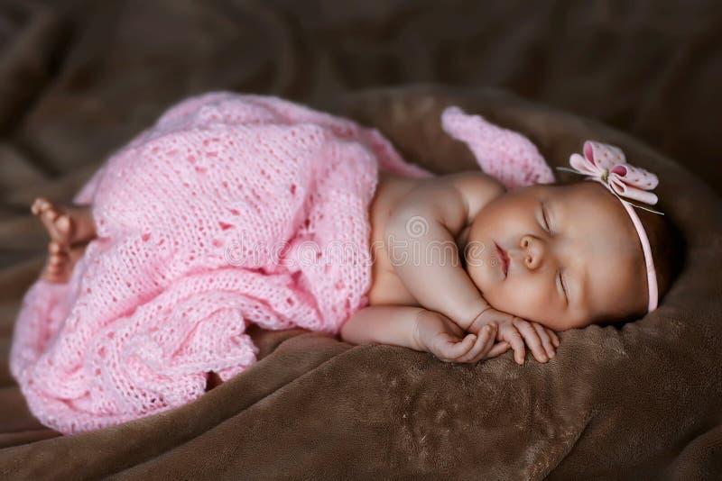 Sonno della ragazza di neonato sveglio, coperto di sciarpa rosa molle, piegata ordinatamente sotto una penna con una piccola test fotografia stock