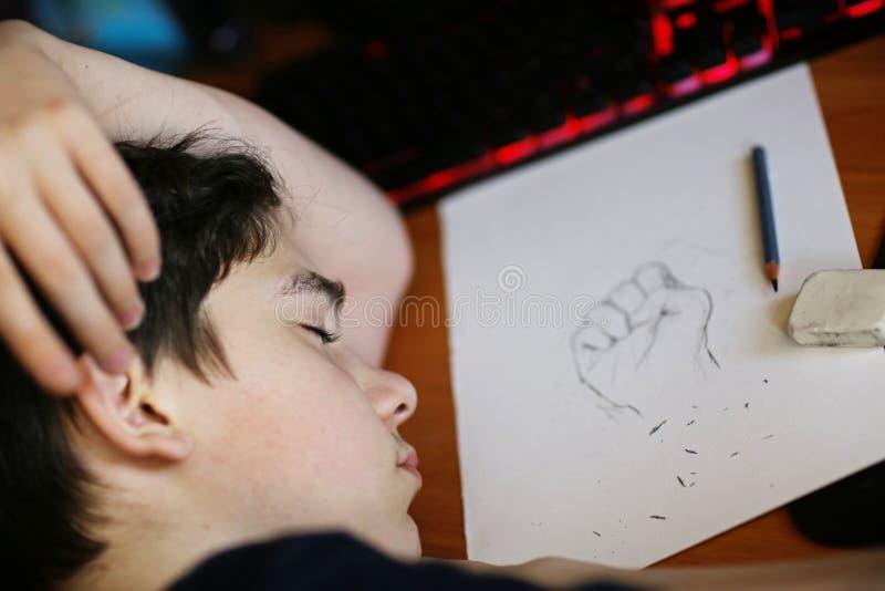 Sonno dello studente della scuola di arte del ragazzo dell'adolescente sul suo disegno di compito immagine stock