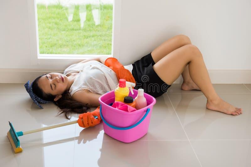 Sonno femminile stanco del proprietario dopo la pulizia della casa fotografia stock libera da diritti