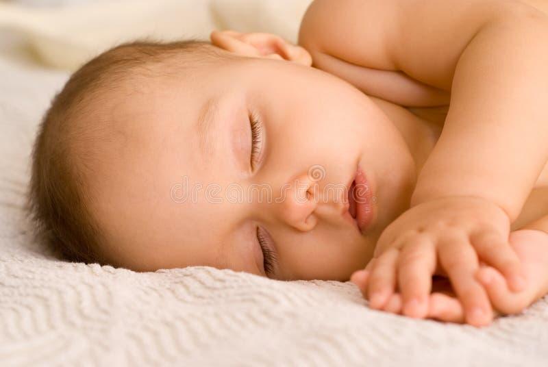 Sonno piacevole del bambino su un bianco immagine stock