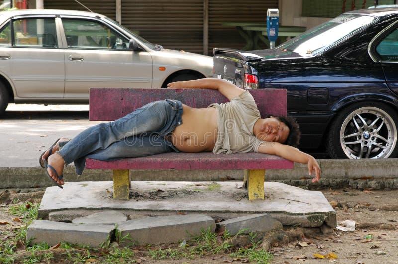 Sonno senza tetto dell'uomo sul banco su fondo urbano Mendicante sulla via Vivendo sulle vie povertà Aiutando quelli più di meno fotografie stock
