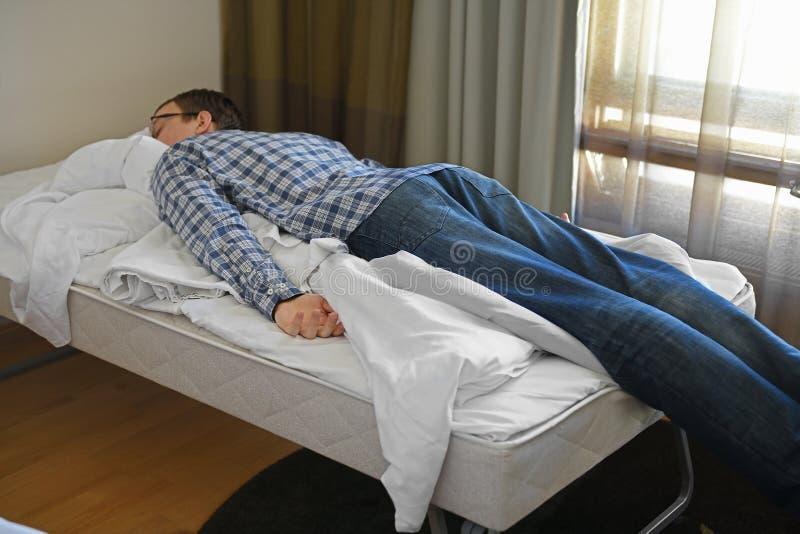 Sonno turistico stanco agghindato sul letto immagine stock