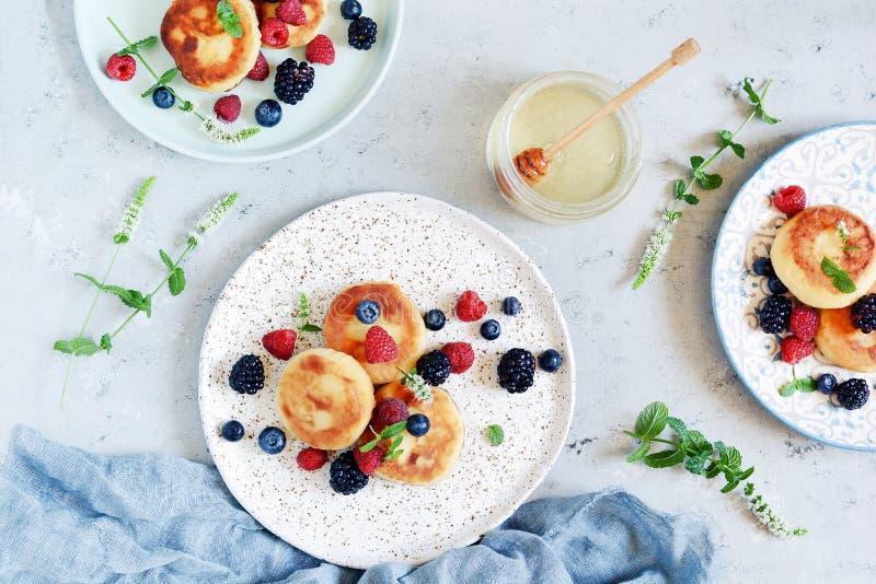 Sonntags-Frühstück mit Käsekuchen, Honig, frischen Beeren und Minze Hüttenkäsepfannkuchen stockfotografie