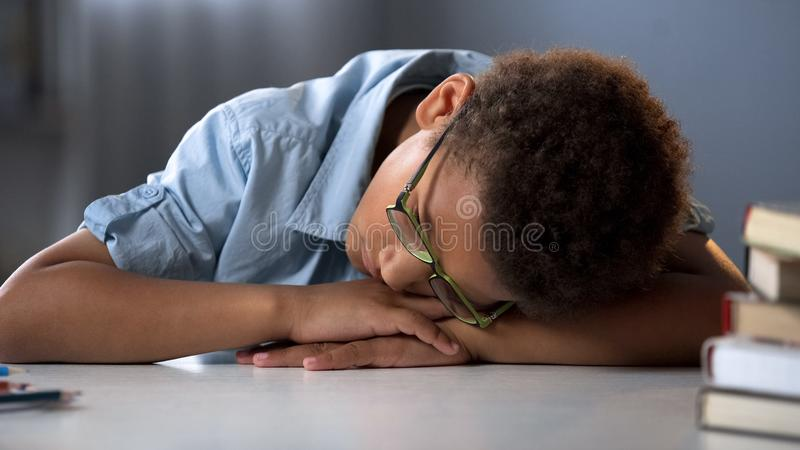 Sono cansado do aluno, sentando-se na mesa, processo educacional duro, menino sobrecarregado imagem de stock