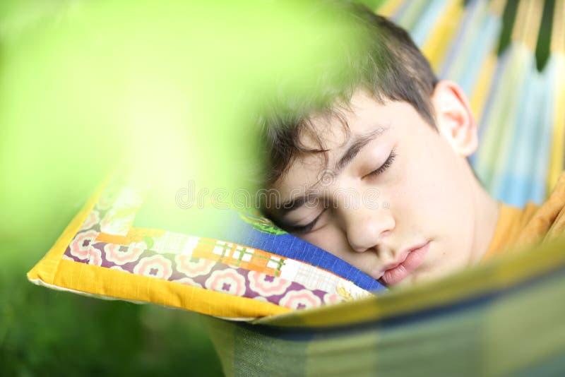 Sono de descanso do menino do adolescente com o livro na rede no jardim verde do verão fotos de stock