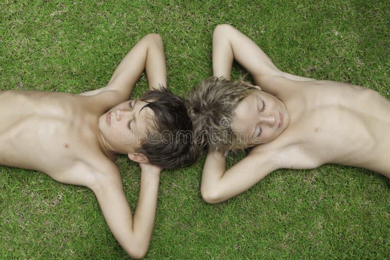 Sono de dois meninos que encontra-se em uma grama verde imagem de stock royalty free