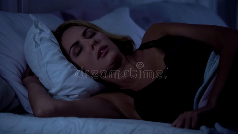 Sono fêmea bonito na cama na noite, descansando após o dia de trabalho duro, ressono fotos de stock
