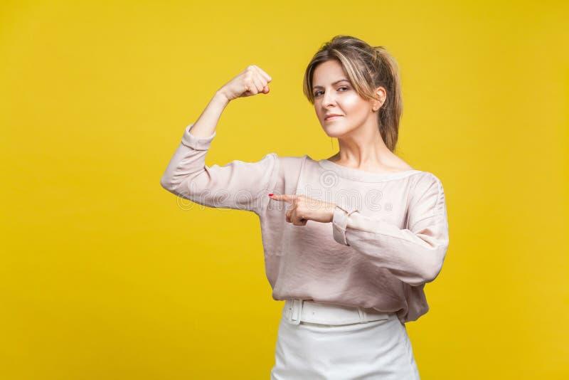 Sono forte Ritratto di una donna potente con i capelli biondi in una camicetta di beige, isolata su sfondo giallo fotografie stock libere da diritti