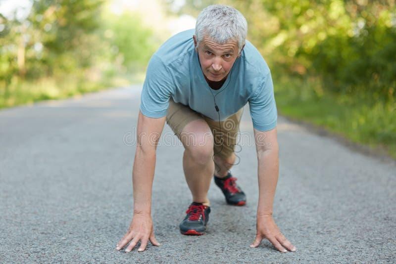 Sono pronto a cominciare! L'uomo senior sicuro sta nella posizione sull'inizio, essendo partecipante della maratona di sport, ind immagini stock