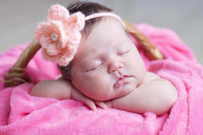 Sono recém-nascido com a flor feita malha na cabeça Close up infantil do bebê que encontra-se na cobertura cor-de-rosa na cesta R foto de stock royalty free