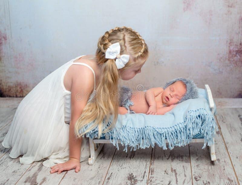 Sono recém-nascido em pouca cama e em sua irmã fotos de stock