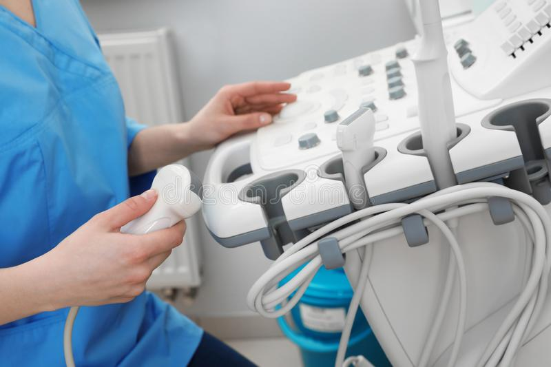 Sonographer operating modern ultrasound machine in clinic. Closeup royalty free stock photography