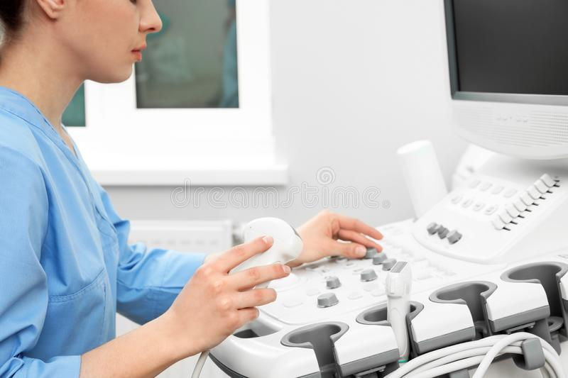 Sonographer operating modern ultrasound machine royalty free stock images