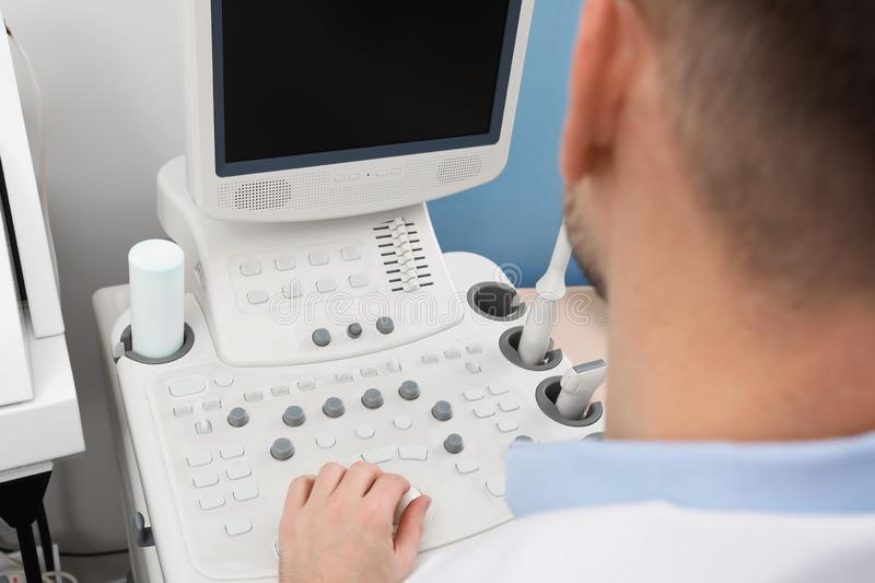 Sonographer operating modern ultrasound machine in clinic stock image