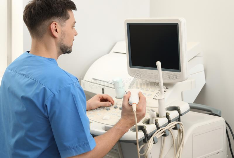 Sonographer operating modern ultrasound machine i stock photos