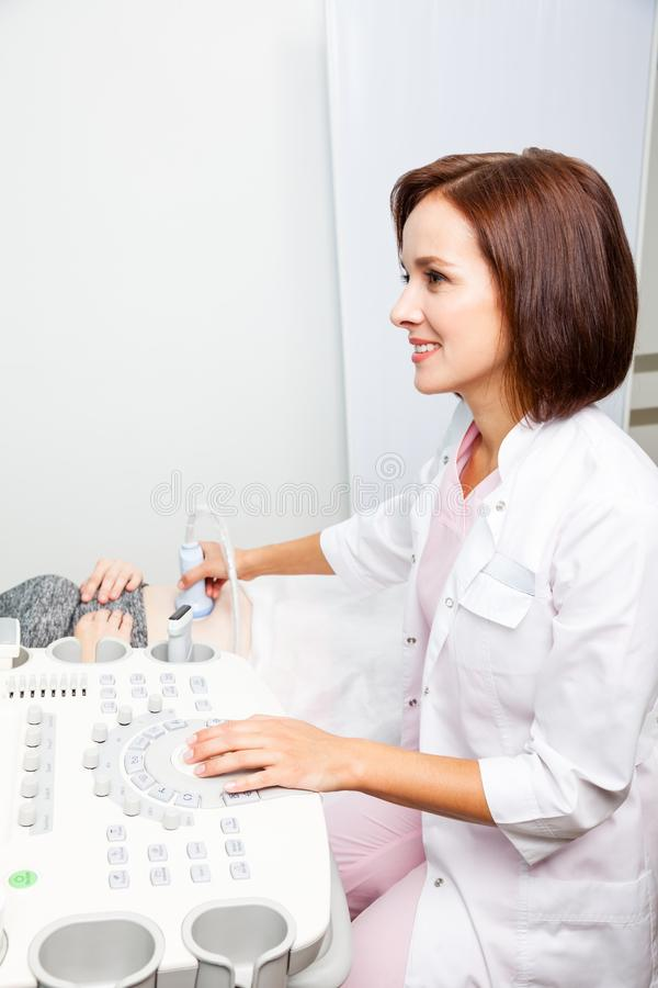 Doctor operating ultrasound machine performing obstetric ultrasonography royalty free stock photos