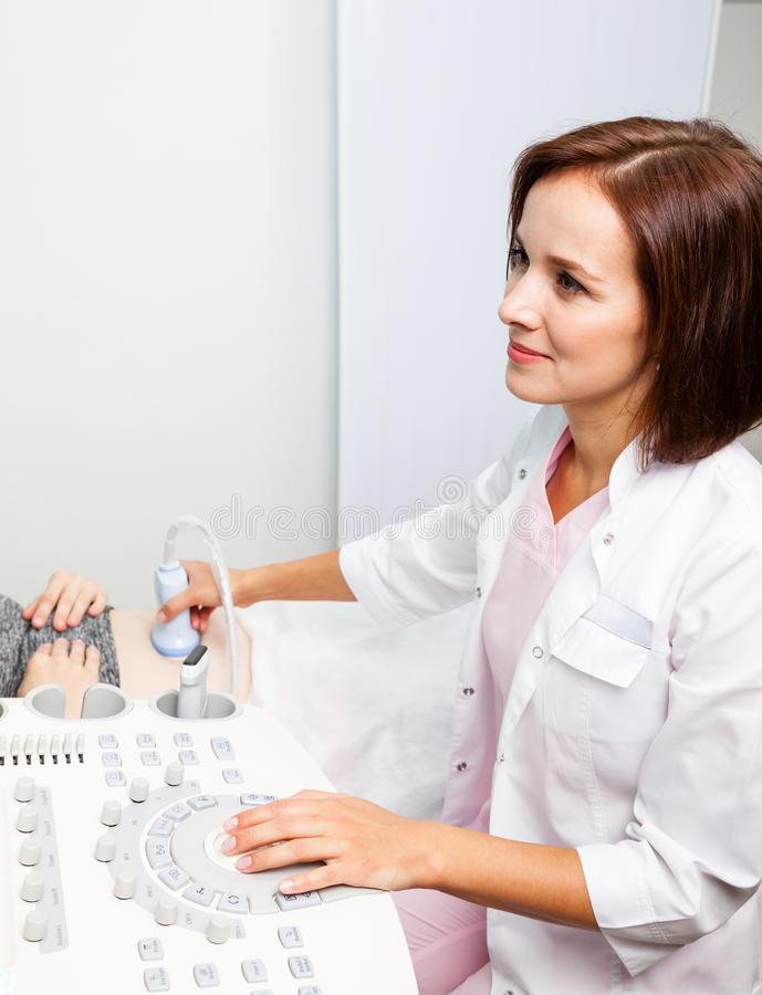 Doctor operating ultrasound machine performing obstetric ultrasonography stock photos