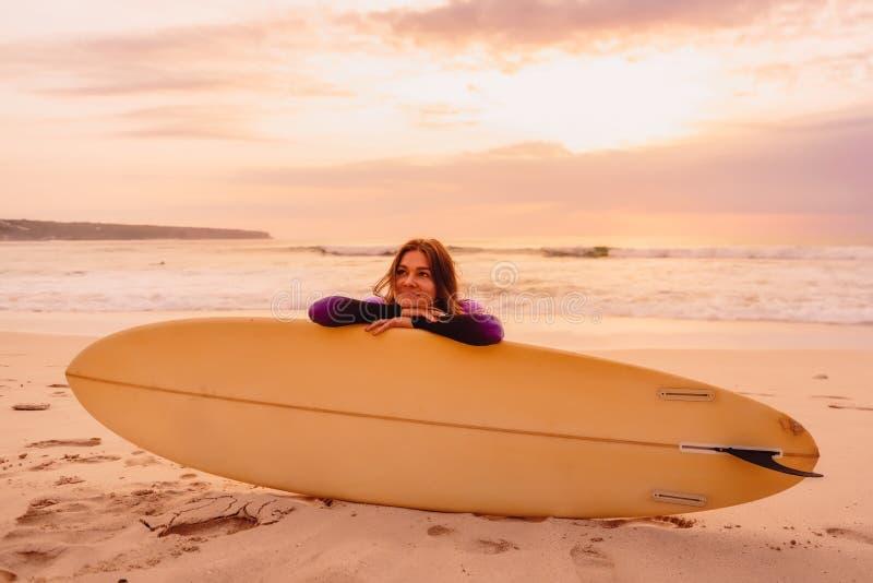 Sonrió una muchacha de la persona que practica surf con la tabla hawaiana en una playa en la puesta del sol imagenes de archivo