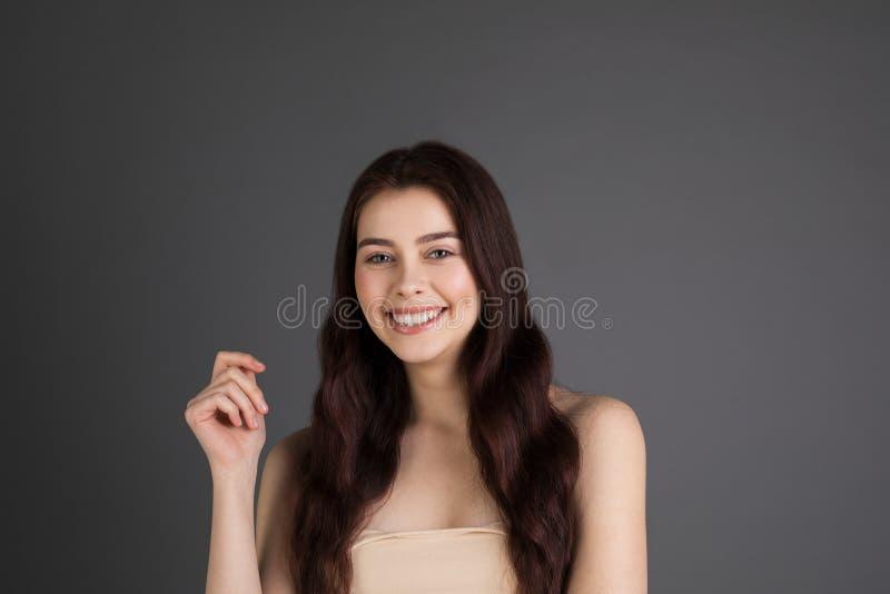 Sonriendo bastante alegre femenino con el pelo moreno, mirando con la satisfacción, siendo feliz foto de archivo