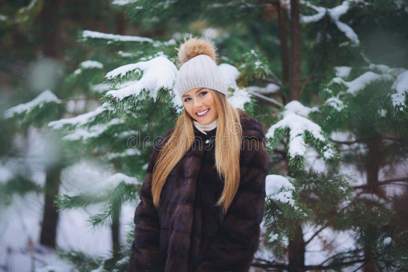 Sonriendo, chica joven feliz que camina en bosque del invierno imagenes de archivo