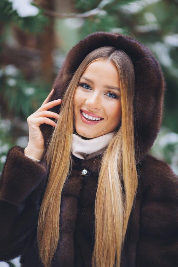 Sonriendo, chica joven feliz que camina en bosque del invierno imágenes de archivo libres de regalías