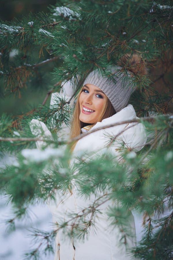 Sonriendo, chica joven feliz que camina en bosque del invierno fotografía de archivo