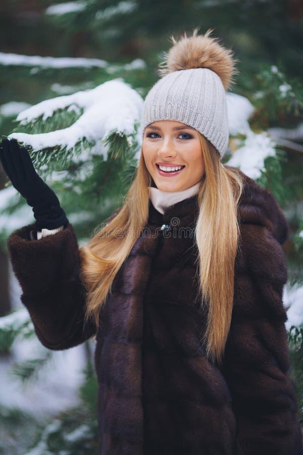 Sonriendo, chica joven feliz que camina en bosque del invierno imagen de archivo