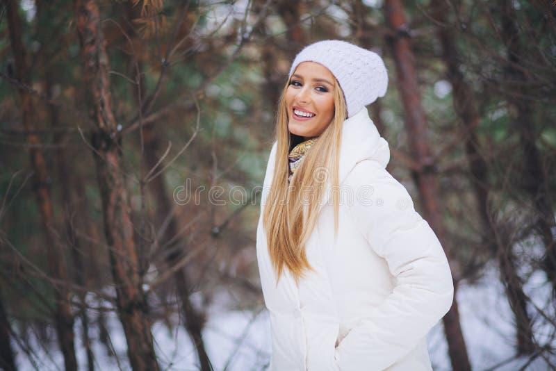 Sonriendo, chica joven feliz que camina en bosque del invierno foto de archivo libre de regalías
