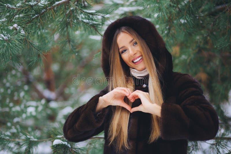 Sonriendo, chica joven feliz que camina en bosque del invierno foto de archivo