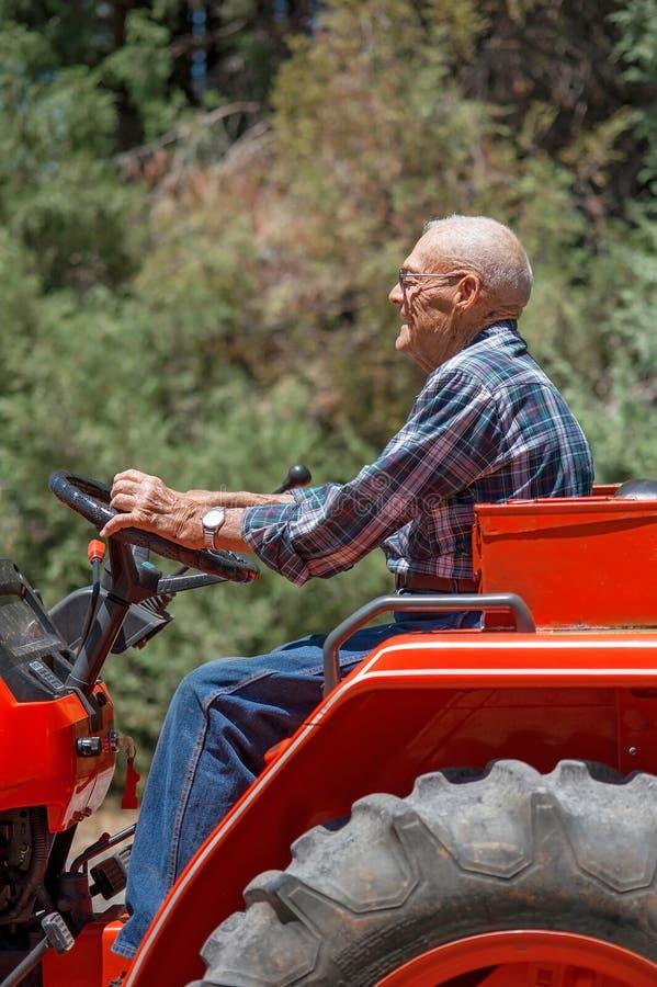 Sonriendo, hombre mayor que actúa un tractor fotografía de archivo