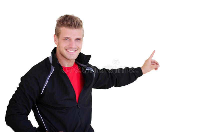 Sonriendo, instructor personal joven que señala el finger en el espacio en blanco imagen de archivo libre de regalías