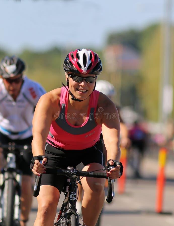 Sonriendo, mujer de ciclo que lleva el top sin mangas rosado fotos de archivo libres de regalías