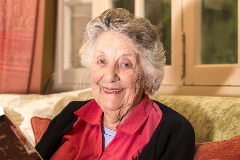 Sonriendo mujer mayor, gris-cabelluda, leyendo en su salón, foto de archivo libre de regalías