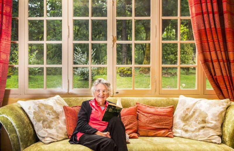 Sonriendo mujer mayor, gris-cabelluda, leyendo en su salón, foto de archivo