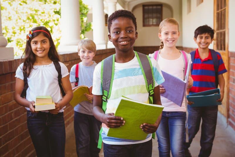 Sonriendo pocos niños de la escuela en pasillo de la escuela imagen de archivo libre de regalías