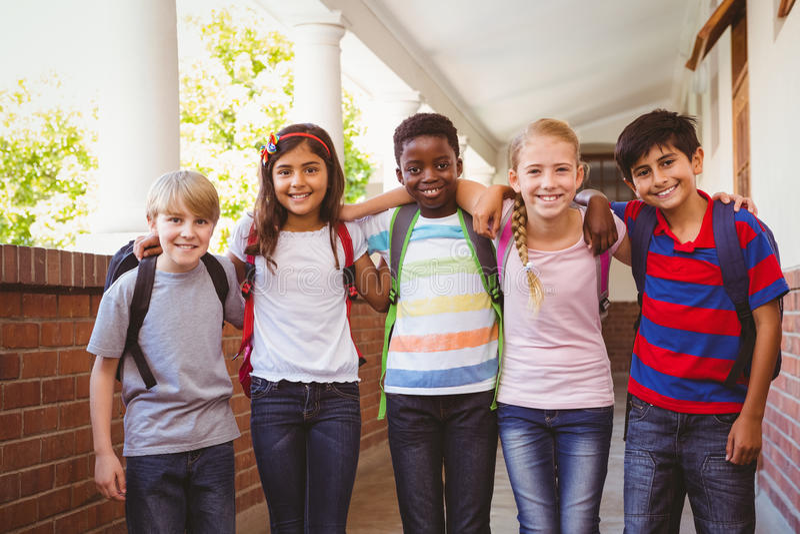 Sonriendo pocos niños de la escuela en pasillo de la escuela imagen de archivo