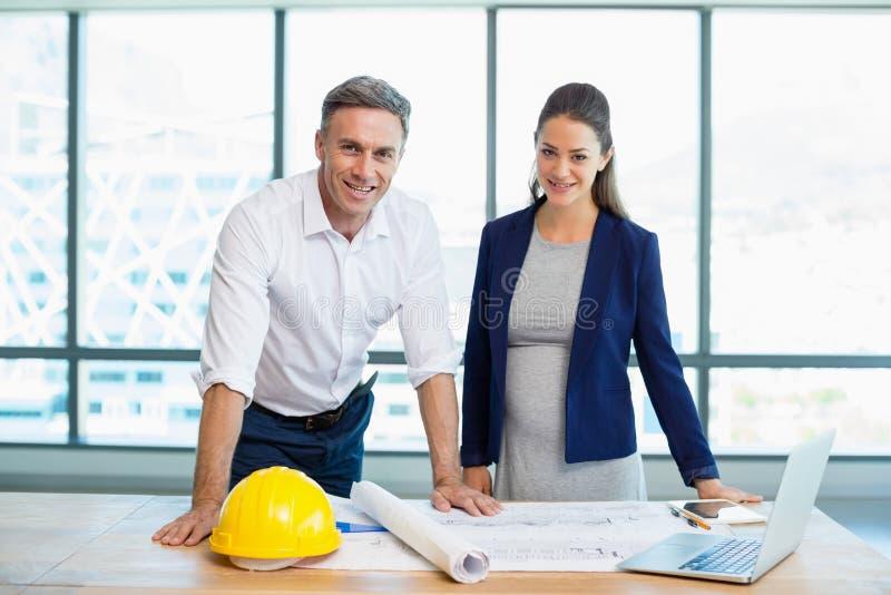 Sonriendo tres arquitectos que se colocan en oficina con el modelo y ordenador portátil en la tabla imagenes de archivo