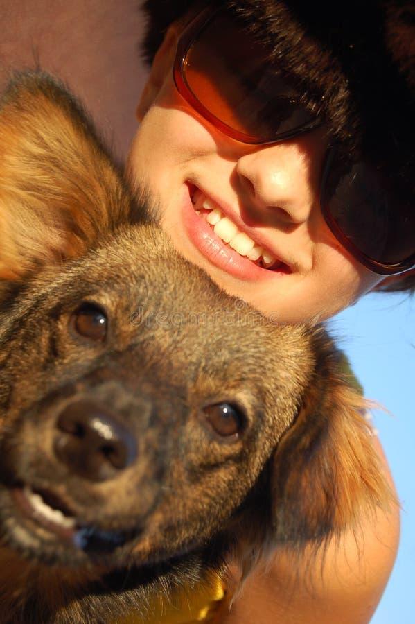 Sonrisa adolescente con un perro foto de archivo