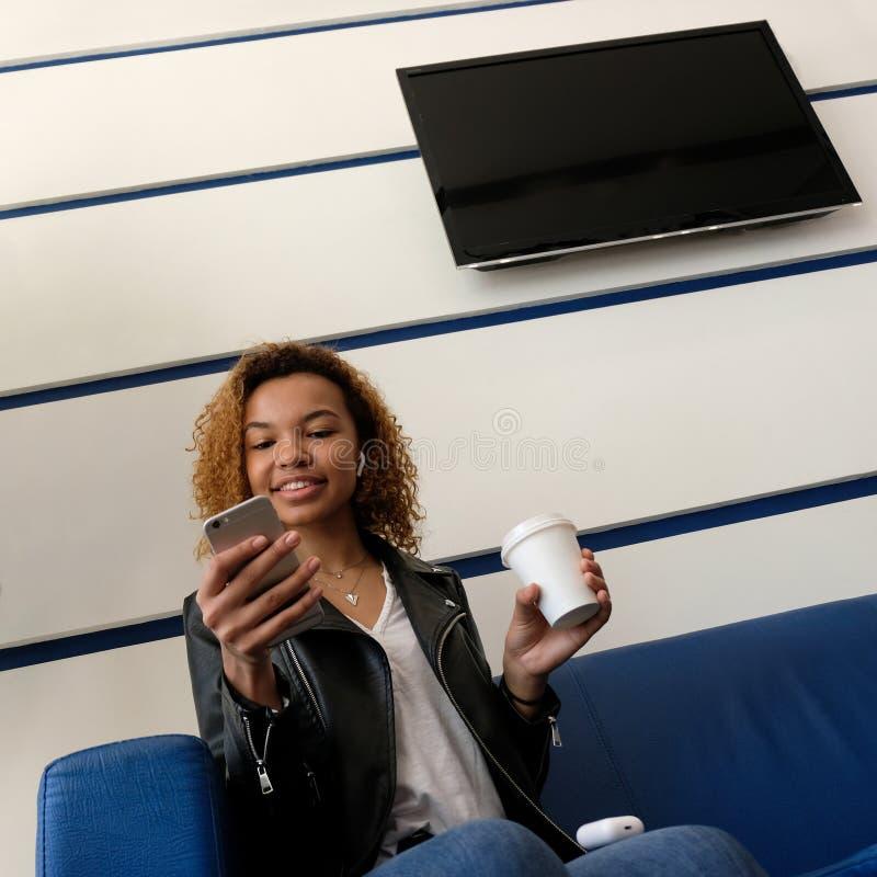 Sonrisa afroamericana de la muchacha, mirando en su teléfono Un vidrio blanco con café a disposición Copyspace TV en una pared bl fotos de archivo libres de regalías