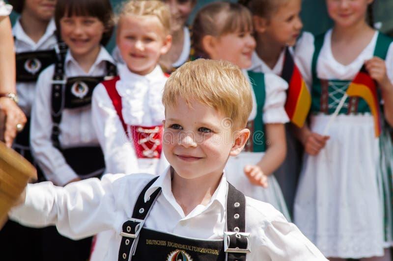 Sonrisa alemana del niño del traje imagen de archivo