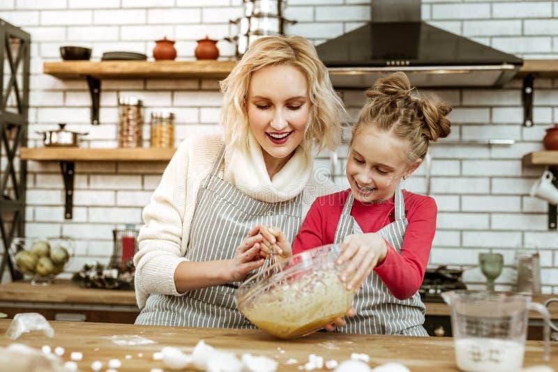 Sonrisa apelando a la mujer que es feliz con su hija de cocinar foto de archivo