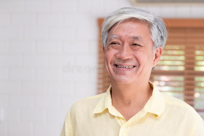 Sonrisa asiática del hombre mayor en sala de estar en casa, feliz envejeciendo en casa concepto imágenes de archivo libres de regalías
