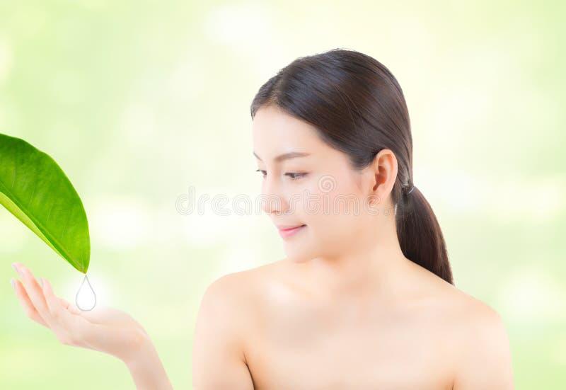 Sonrisa asiática hermosa de la mujer joven que muestra la mano del gesto que sostiene el agua del descenso para la hoja foto de archivo libre de regalías