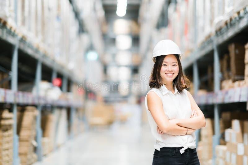 Sonrisa asiática joven hermosa del ingeniero o del técnico, fondo de la falta de definición del almacén o de la fábrica, industri fotografía de archivo
