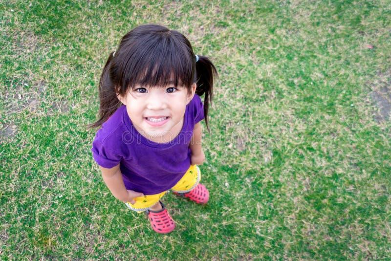 Sonrisa asiática linda del niño en hierba verde foto de archivo